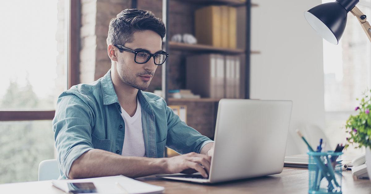 Homem olhando a tela de um notebook
