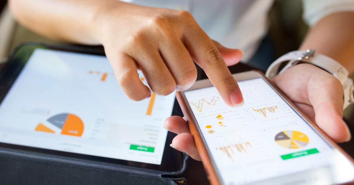 Aparece uma mão usando um celular e um tablet com alguns gráficos