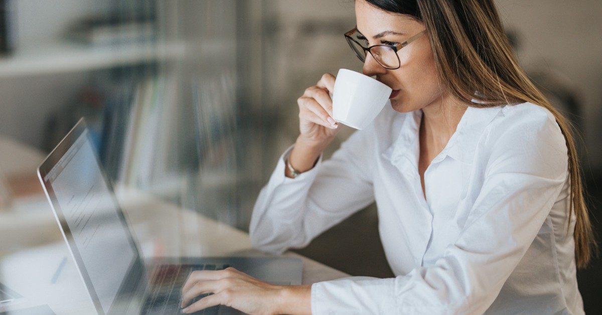 Mulher olhando a tela de um computador e tomando café