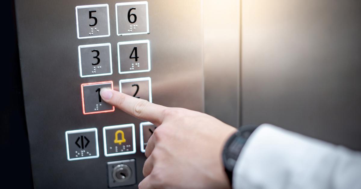 uma mão apertando os números de um elevador