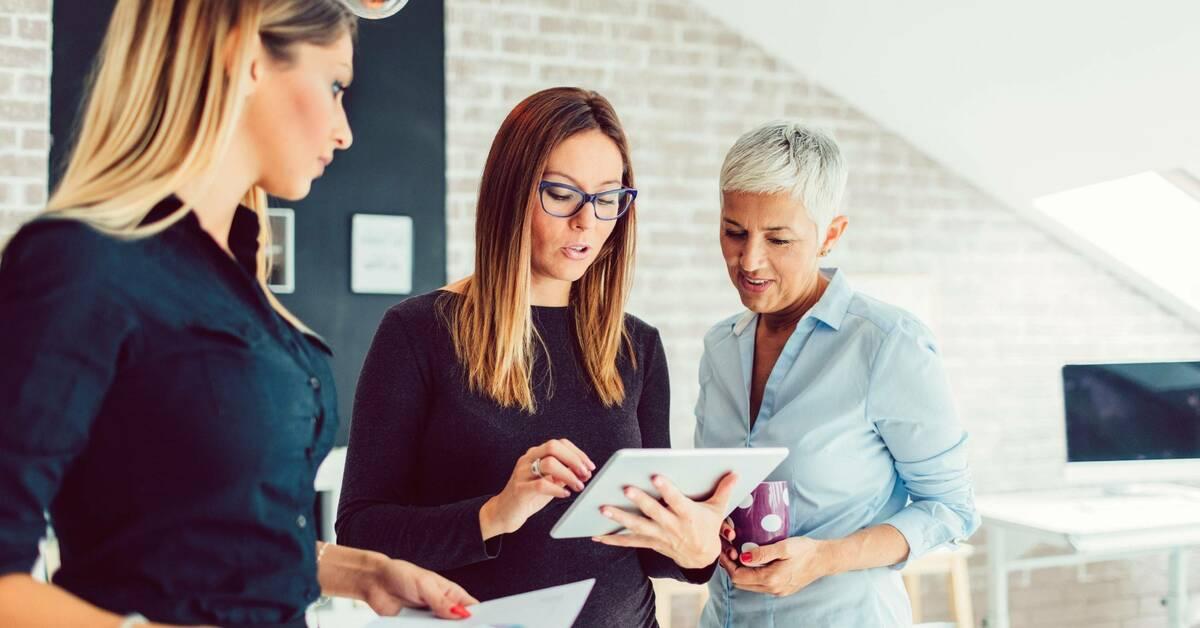Três mulheres olhando para um tablet