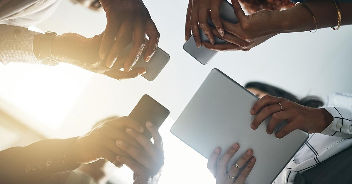 várias mãos com diferentes dispositivos