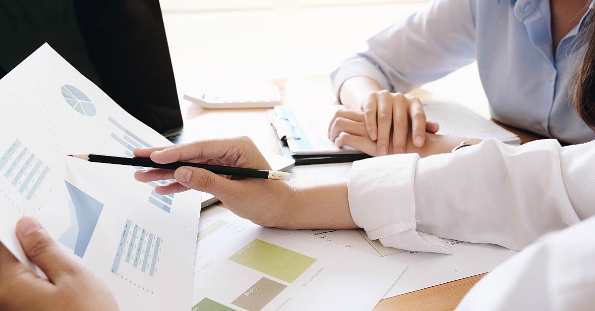 A imagem mostra uma mão segurando um papel com alguns gráficos
