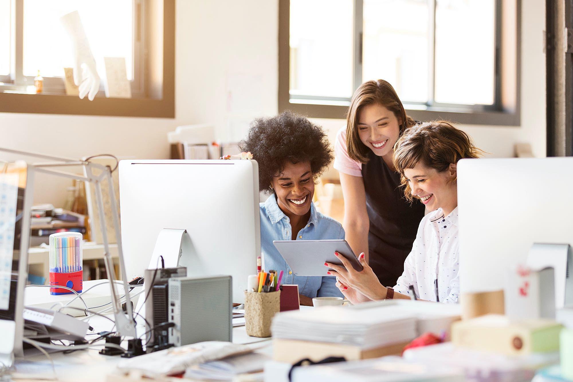 Três mulheres conversando em um ambiente corporativo