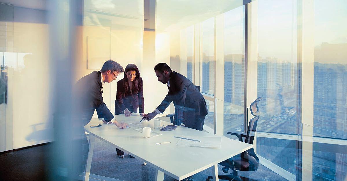 Três pessoas conversando em um ambiente corporativo