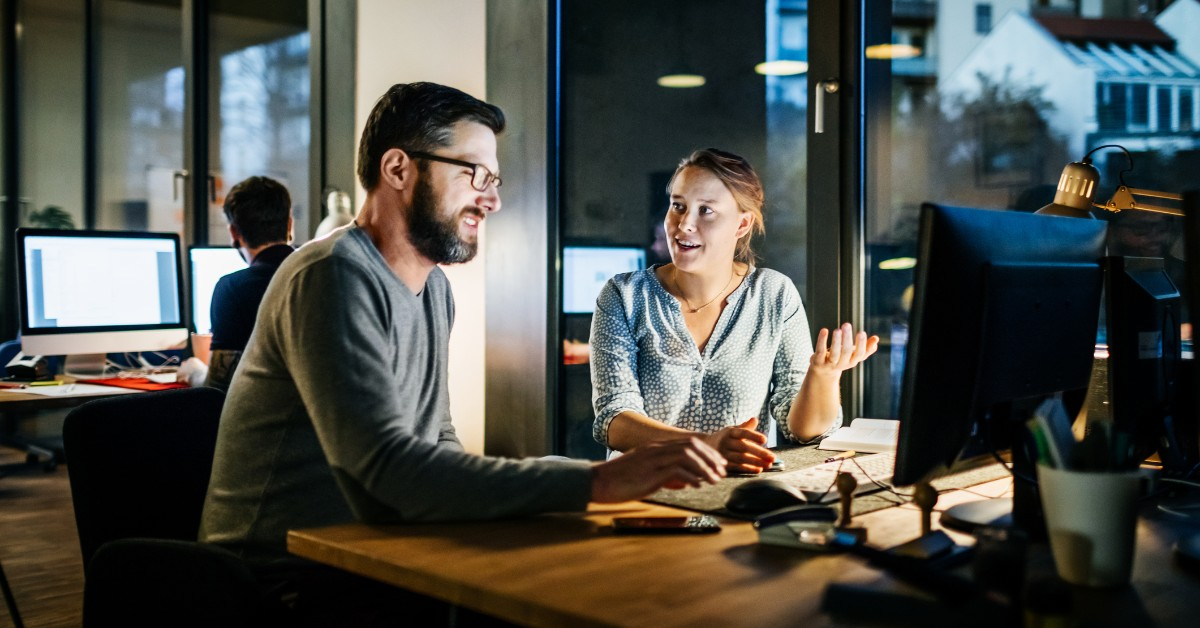 Um homem e uma mulher olhando para a tela de um computador