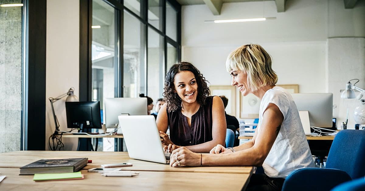 duas mulheres conversando e olhando para a tela de um computador